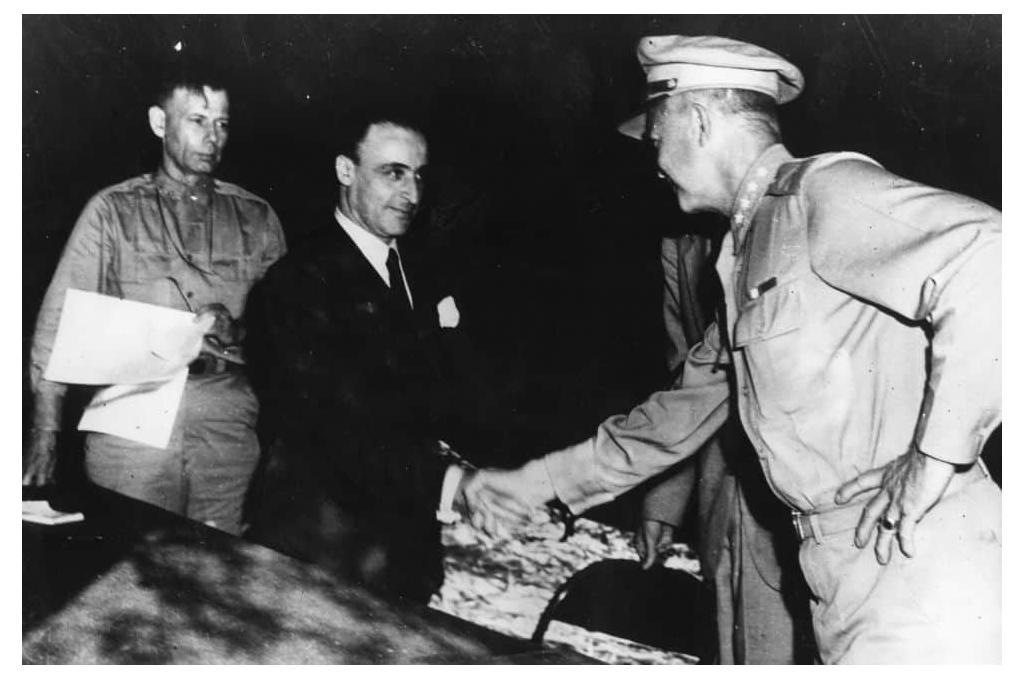 General Giuseppe Castellano, in civilian attire, shakes hands with General Eisenhower after signing the armistice.