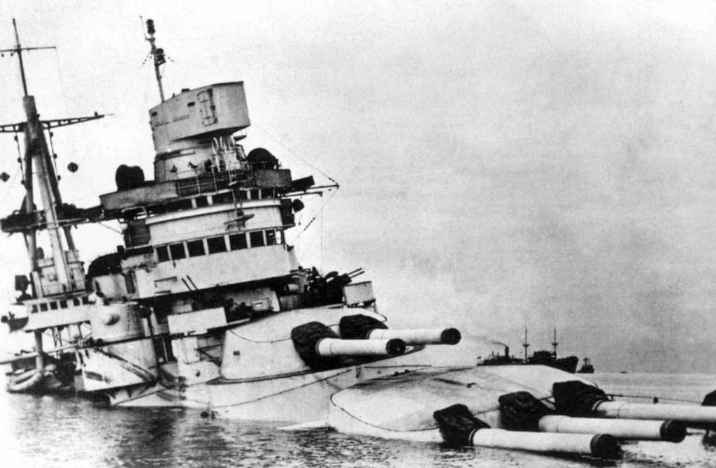 The Conte di Cavour sinks in shallow water.
