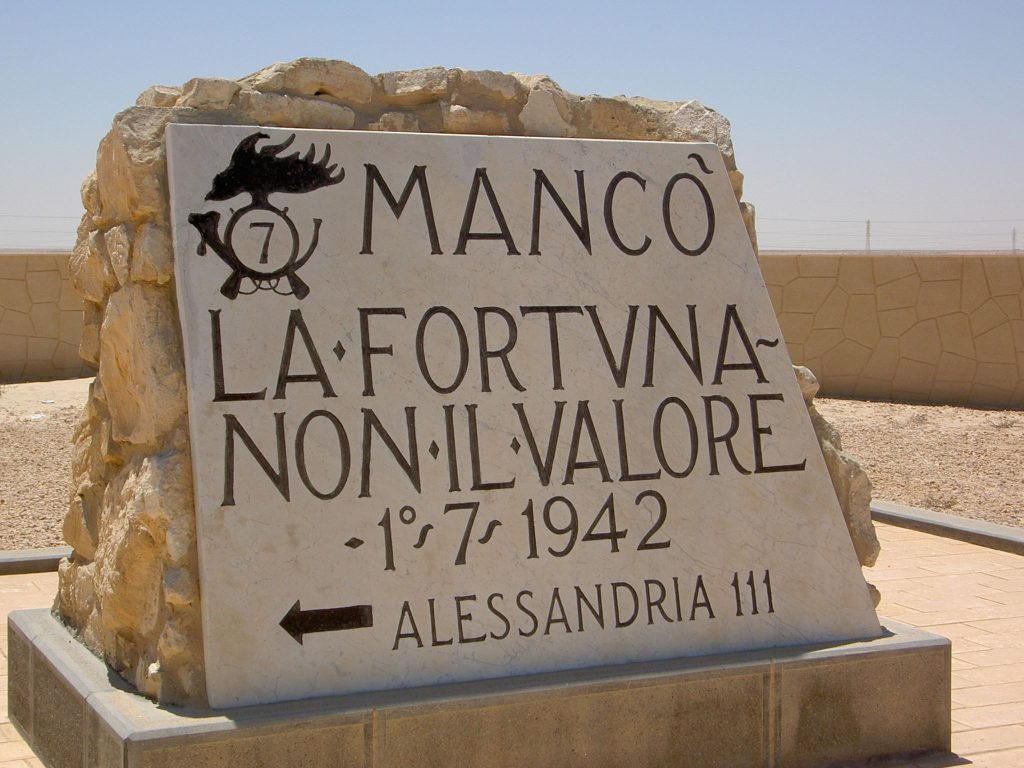 "Commemorative stone put up by the 7th Bersaglieri Regiment on the road from Alexandria to El Alamein. The sign translates to ""Lack of fortune, not valor."" I"