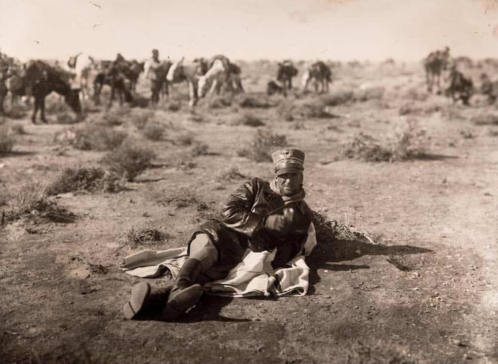 "General Rodolfo Graziani, ""The Butcher of Fezzan"" drinking a beverage (possibly coffee) while relaxing on the desert floor of Italian Cyrenaica, Libya. Photograph taken circa 1931."