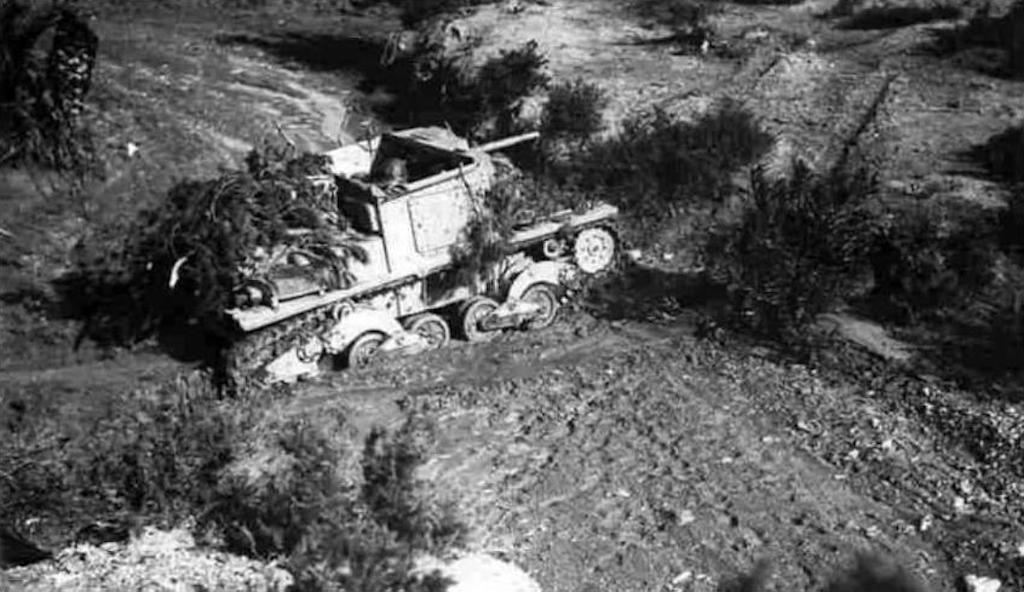 A Semovente L40 camouflaged with branches and shrubs.