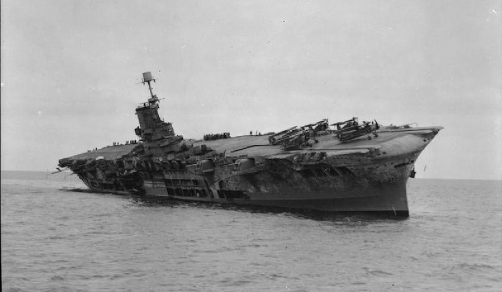 HMS Ark Royal lists severely before finally sinking.