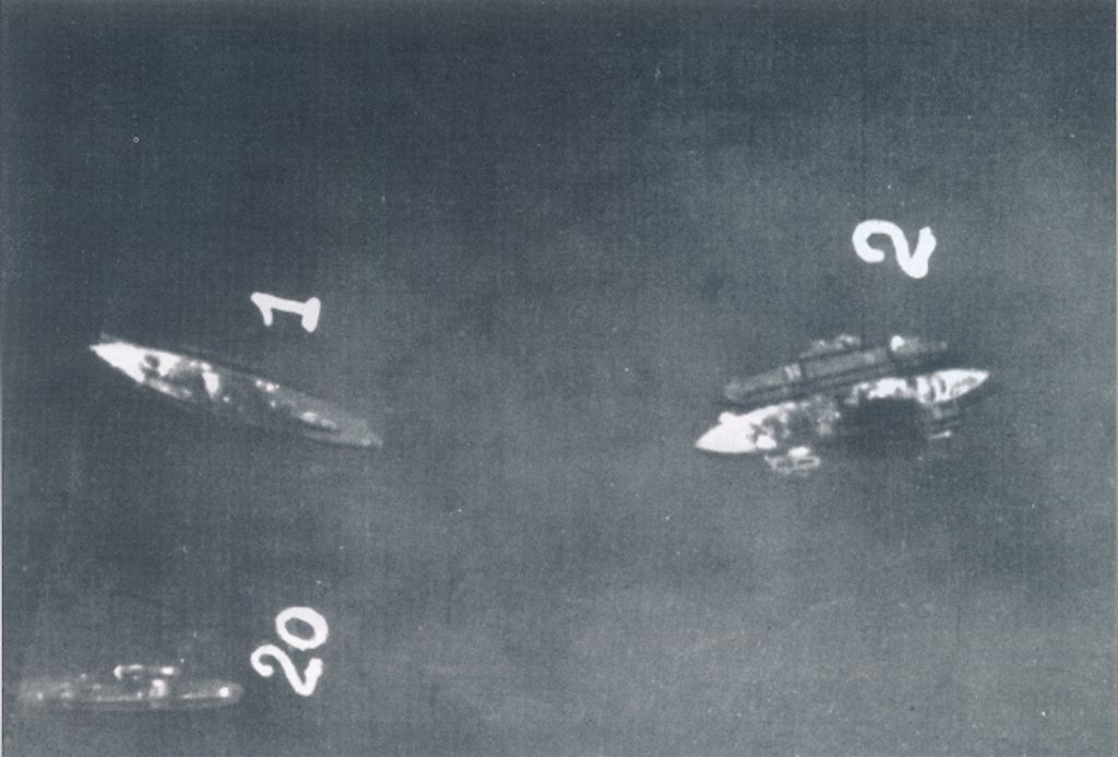 Aerial image of Battleships Valiant and Queen Elizabeth sunk in shallow water.