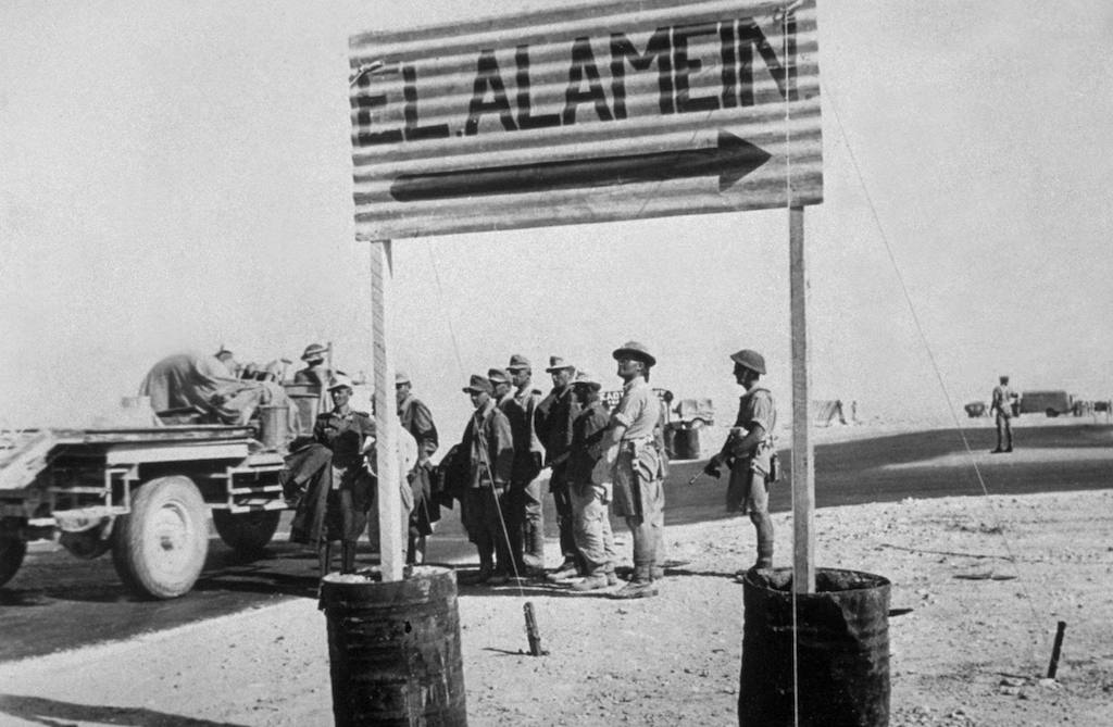 German prisoners under a sign for El Alamein.