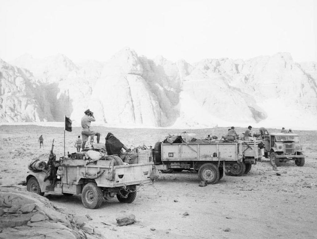 LRDG–SAS in trucks halted at the massive rock outcrop of Gilf Kebir during Operation Agreement.